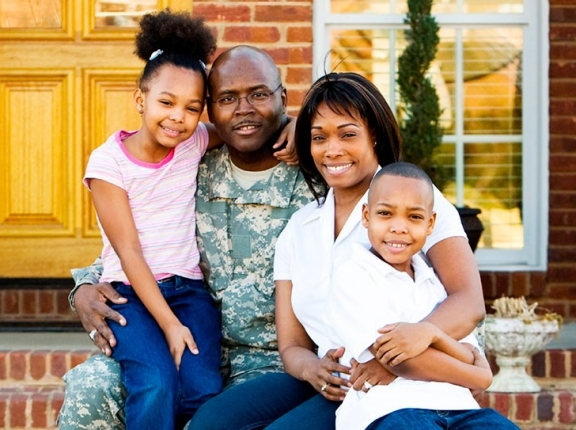 A military family sits in front of their house, photo by Department of Defense