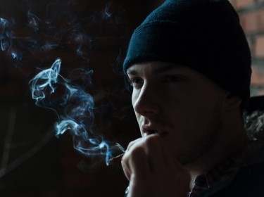 A young man in a cap smokes a cigarette