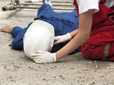 A worker giving first aid after an accident