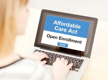 Woman on laptop enrolling in insurance plan through the Affordable Care Act site