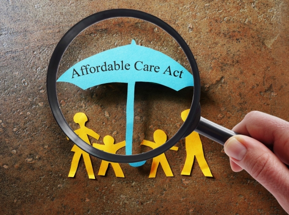 Paper family under a Affordable Care Act umbrella with magnifying glass, photo by zimmytws/iStock