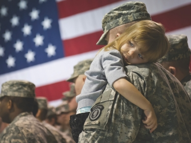 U.S. Army soldier holds his daughter after a deployment ceremony at the Alaska National Guard Armory