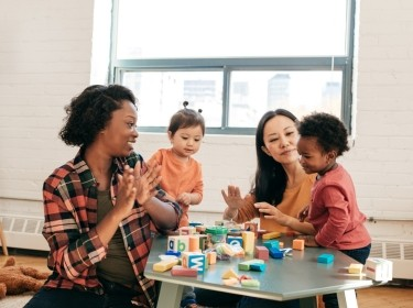 Two women sit at a table with two young children playing with blocks