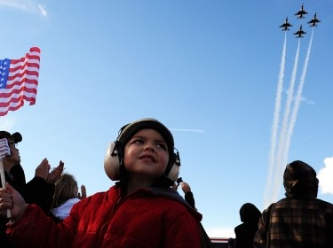 A boy waves his U.S. flag as the U.S. Air Force Air Demonstration Squadron Thunderbirds fly in the diamond formation during an Aviation Nation airshow at Nellis Air Force Base, Nev. Nov. 10, 2012