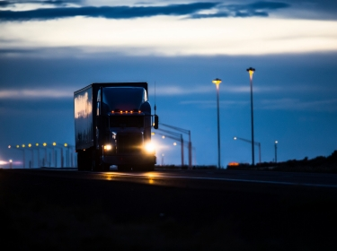Commercial truck driving down the highway at night