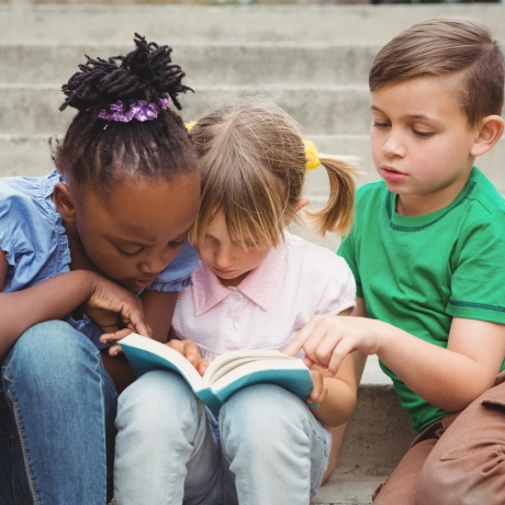 Three children sitting on steps and reading a book, photo by WavebreakMediaMicro/Fotolia