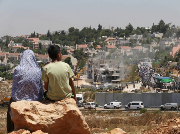 Palestinians watch Israeli heavy machinery demolishing vacant apartment blocs by order of Israel's high court, in the West Bank Jewish settlement of Beit El near Ramallah July 29, 2015, photo by Mohamad Torokman/Reuters