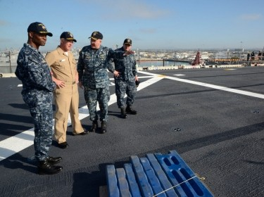 Vice Adm. Thomas S. Rowden, commander of Naval Surface Forces, surveys work done on the flight deck of the amphibious assault ship USS Boxer (LHD 4) during a visit