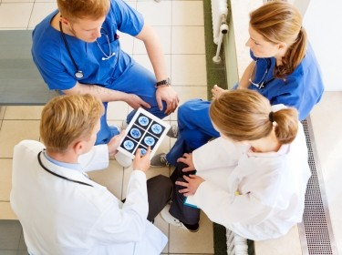 Doctor using a digital tablet to show results to a team of medical staff