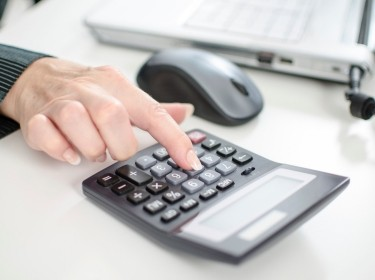 Woman's finger on a calculator with laptop and mouse in the background