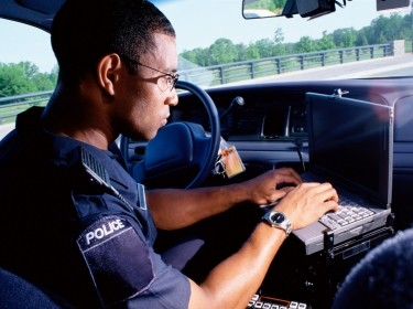 A police officer working on a computer in a patrol car