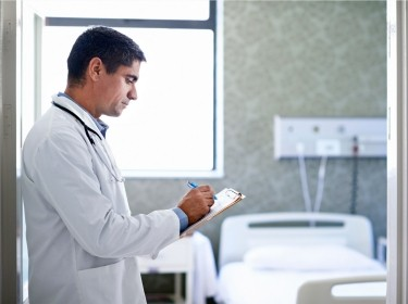 Doctor filling out a patient's chart in front of an empty hospital room