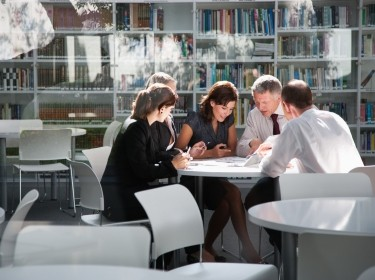 Business people meeting in a library, seen from outside a window