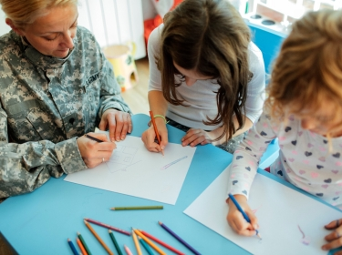 Military mom coloring with her two girls