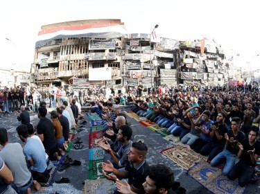 Sunni and Shi'ite Muslims attend prayers during Eid al-Fitr as they mark the end of the fasting month of Ramadan, at the site of a suicide car bomb attack over the weekend in Baghdad, Iraq, July 6, 2016, photo by Thaier Al-Sudani/Reuters