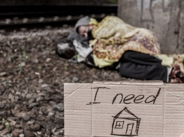 Homeless person sleeping on the ground, with a cardboard sign asking for a home in the foreground