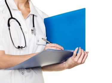 Close up of doctor writing in a blue folder