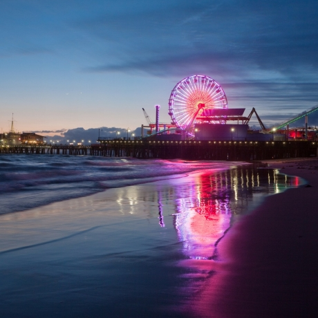 The Santa Monica Pier in California, illuminated at night with a reflection on shoreline, photo by davemantel/Getty Images