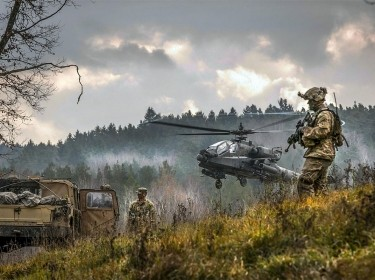 An AH-64 Apache attack helicopter takes off near soldiers participating in a training exercise at Grafenwoehr, Germany, November 18, 2017