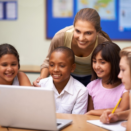A teacher and four students looking at a laptop, photo by PeopleImages/Getty Images
