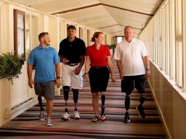 Four adults wearing prosthetics