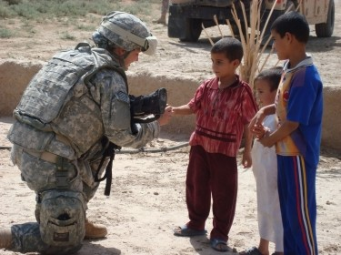 A U.S. soldier tends to Iraqi children during a mission in al-Kut, Iraq, September 19, 2008