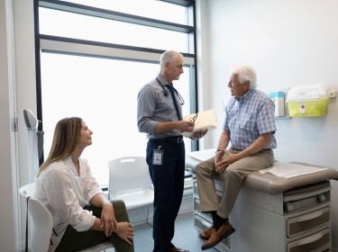 Doctor consulting with an elderly patient while a female family member looks on