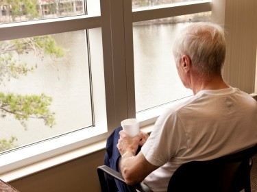 Elderly man holding a cup of coffee, looking out the window