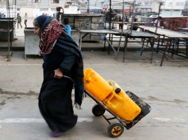 A Palestinian woman drags a cart loaded with water containers after filling them from a public tap in the city of Rafah in the southern Gaza Strip, February 28, 2017