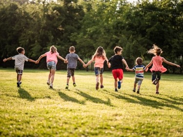 Back view group of children running in park at sunny day