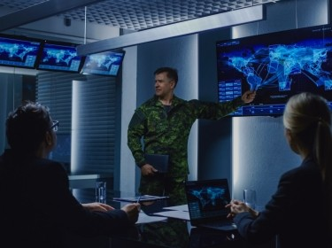 Military leader briefs a team of government officials, photo by Gorodenkoff/Adobe Stock