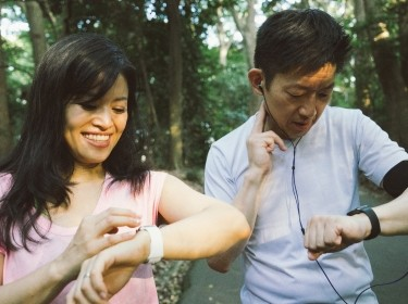 Two people checking data on their smart watches while exercising outdoors