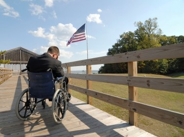Soldier in wheelchair with U.S. Flag in distance