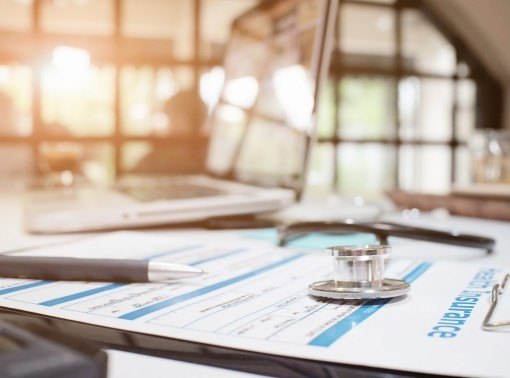 Stethoscope on insurance policy with medical insurance, selective focus