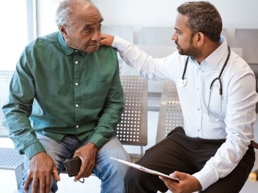 Older gentleman talks with a male doctor, photo by izusek/Getty Images