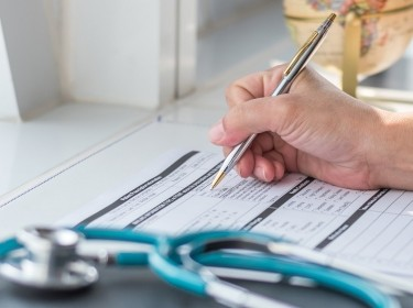 Doctor writing on medical care form with stethoscope in foreground, photo by Chinnapong/Getty Images