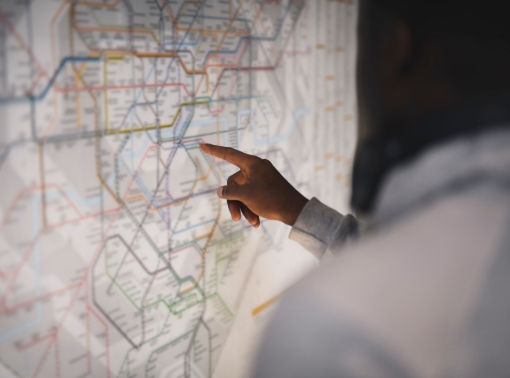 Person pointing at a public transit map, photo by Rawpixel/Getty Images