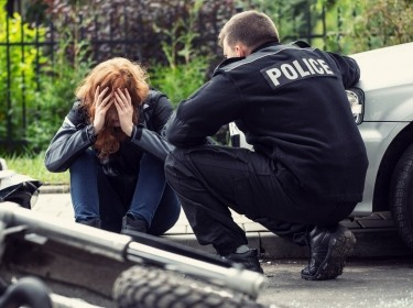 A policeman talks to a distressed person on the street, photo by KatarzynaBialasiewicz/Getty Images