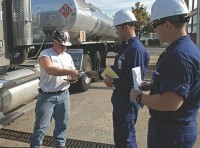 A truck driver shows his transportation worker identification credentials to Coast Guard Petty Officer 1st Class Kevin Parrington and Ens. Cassidy Childs at the Motiva Enterprises fuel terminal. Photo by PA2 Lauren Jorgensen/Coast Guard First District Public Affairs