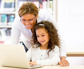a teacher or principal with a student looking at a laptop