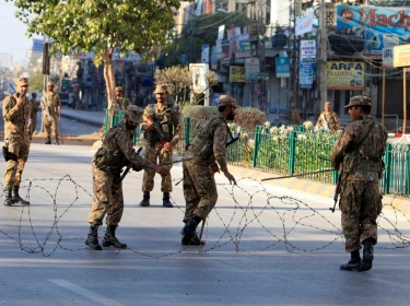 Pakistani soldiers place barbwire to secure a street during a curfew in Rawalpindi