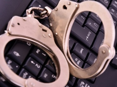 Police handcuffs on a computer keyboard