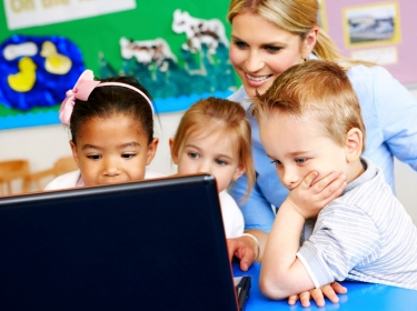 Three preschoolers looking at a laptop with their teacher