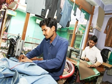 Two Indian men working in a textile shop