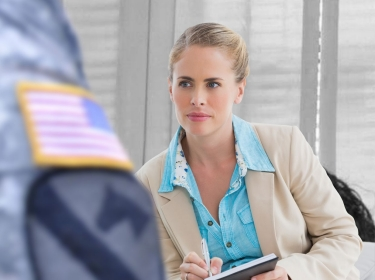 A therapist counseling a soldier in uniform