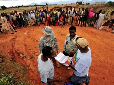 A service member and interpreter talk with residents about malaria prevention in Ethiopia