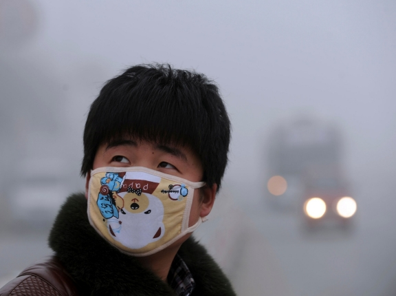 A man wearing a mask looks up as he walks on a street on a foggy day in Bozhou, China, January 30, 2013, photo by China Daily/Reuters