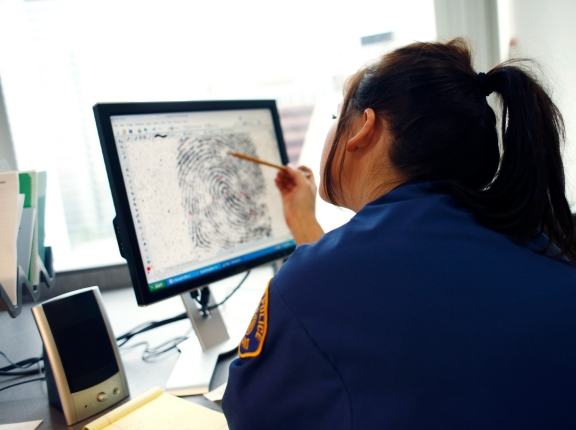 A police officer examining a fingerprint on a monitor, photo by pkripper503/iStock