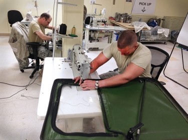 A Soldier repairs tears on a humvee door using a long-arm sewing machine
