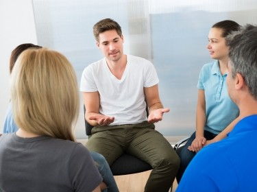 A young man talks at a group counseling session